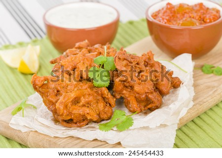 Onion Bhajis - South Asian fritters served with lime chutney and mint raita. - stock photo