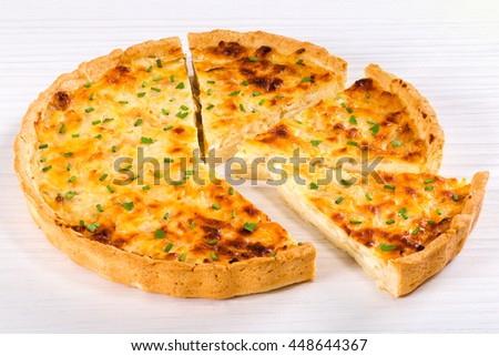 onion cheese quiche or pie sprinkled with parsley and spring onion, cut into portion, on white worktop, view from above - stock photo