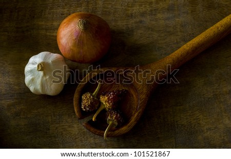Onion, garlic and chilies on wooden tray - stock photo
