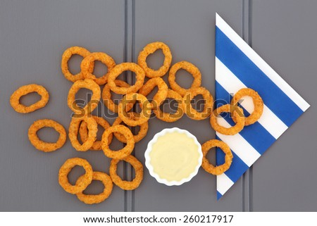 Onion ring snack food with mayo dip and striped napkin. - stock photo