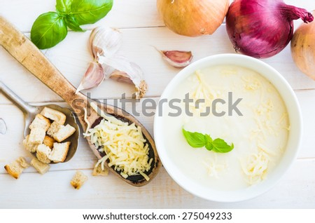 onion soup puree in a white plate with toasts and cheese on the table - stock photo