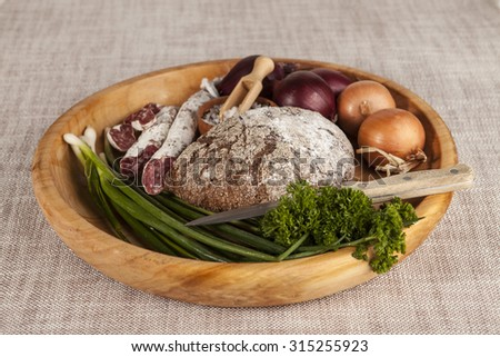 Onions, brown bread wooden tray with parsley and salt, salami celery ,knife. - stock photo