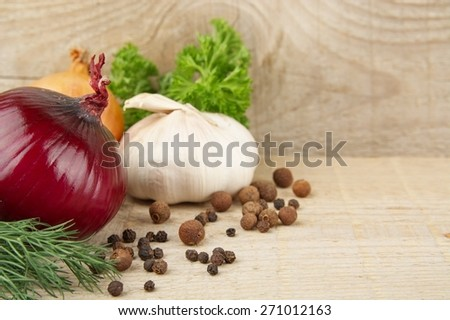 Onions,red onions,dill,parsley,allspice,garlic and black pepper on wooden planking - stock photo