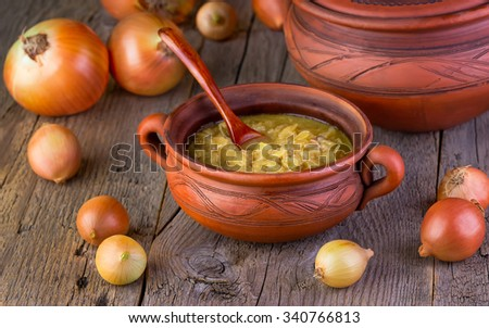 onions soup in a plate on a wooden background - stock photo