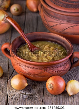 onions soup in pottery on a  wooden background - stock photo