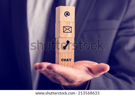 Online business communications concept with a businessman holding a stack of four wooden cubes balanced on his palm displaying icons for email, a web address, mail, telephone and chat. - stock photo