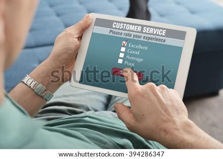 Online customer service satisfaction survey on a digital tablet - stock photo