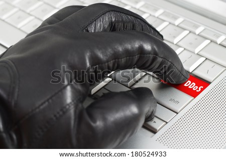 Online distributed denial services attack  concept with hand wearing black leather glove pressing enter key on metallic laptop keyboard - stock photo