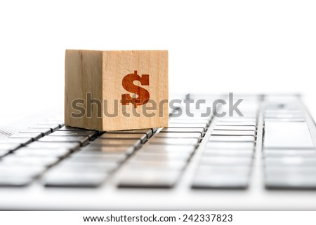 Online earnings concept with a wooden block with dollar sign standing on a computer keyboard, with copyspace. - stock photo