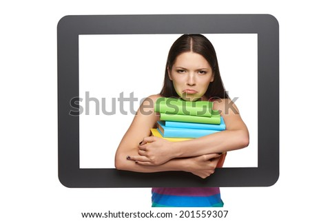 Online library / learning concept. Discontent young woman holding stack of books through tablet frame, over white background - stock photo
