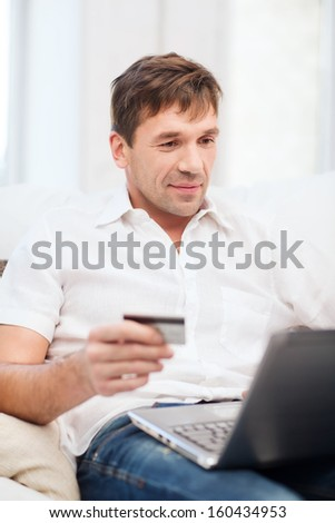 online or internet shopping concept - smiling man with laptop and credit card at home - stock photo