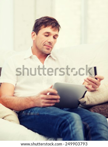 online or internet shopping concept - smiling man with tablet pc and credit card at home - stock photo