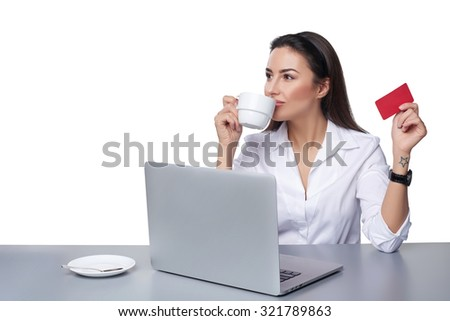 Online payment shopping concept. Business woman sitting at table with laptop, holding empty credit card going to pay online, drinking coffee, isolated on white background - stock photo
