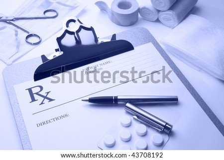 Online rx prescription concept pills pen stethoscope and bandages blue tone - stock photo