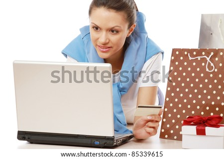 Online shopper lying on floor with laptop isolated - stock photo