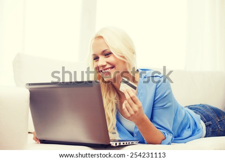online shopping, banking and technology concept - smiling young woman with laptop computer and credit card - stock photo