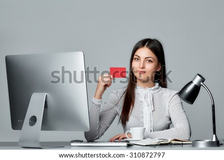 Online shopping concept. Beautiful young woman sits by the table with computer showing blank credit card, isolated on grey background. - stock photo