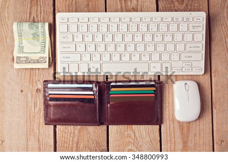 Online shopping concept with wallet, money and keyboard on wooden background. View from above - stock photo