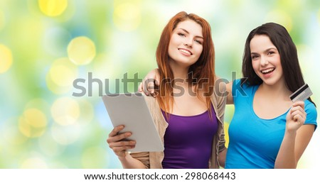 online shopping, e-money, commerce, people and technology concept - two smiling teenage girls or young women with tablet pc computer and credit card over green lights background - stock photo