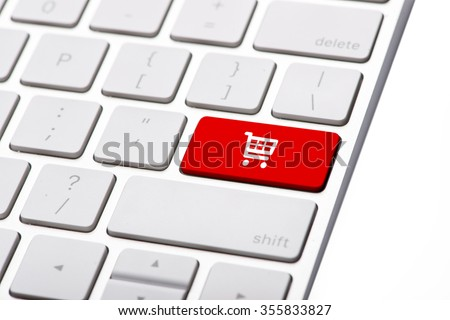 online shopping or internet shop concepts, with shopping cart symbol. Shop online business concept. Red shopping cart button or key on white keyboard - stock photo