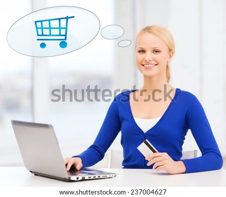 online shopping, people and technology concept - smiling young woman with laptop computer, credit card and text bubble with trolley - stock photo