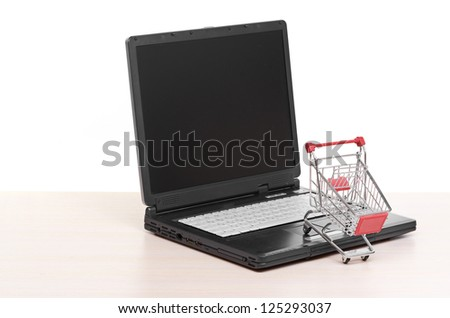 Online shopping. trolley on laptop - stock photo