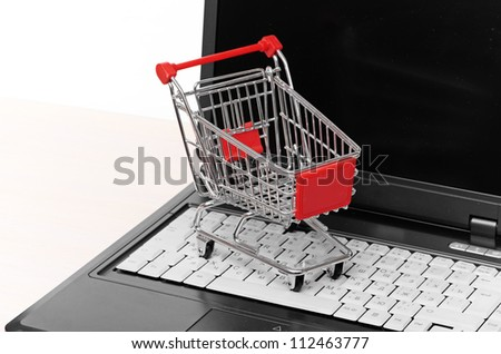 Online shopping. trolley on laptop on white - stock photo