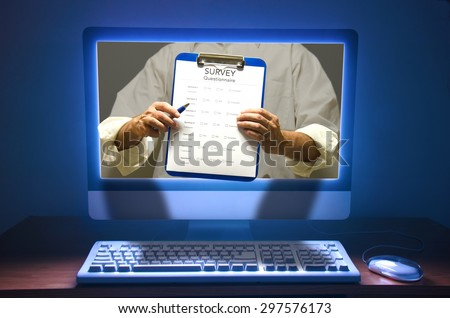 Online survey questionnaire poll test scene showing the questionnaire's clipboard coming out of the computer screen.  - stock photo
