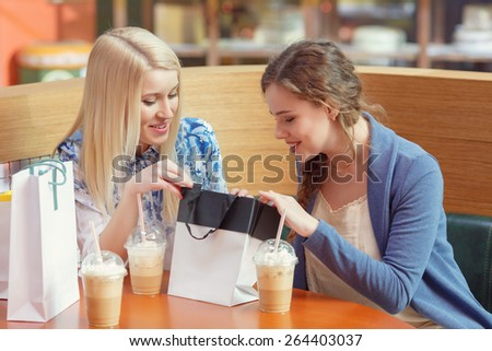 Only best emotions from shopping. Two young girls examining their purchases with smiling expression on their faces - stock photo