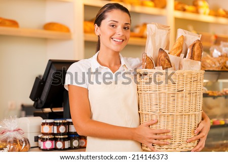 Only fresh bread for our customers. Beautiful young woman in apron holding basket with bread and smiling while standing in bakery shop - stock photo