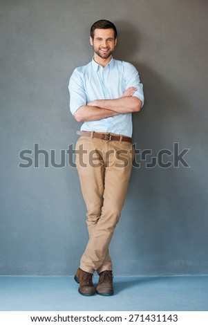 Only positive emotions. Full length of handsome young man in shirt keeping arms crossed and smiling at camera while standing against grey background  - stock photo
