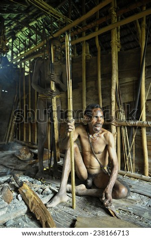 ONNI VILLAGE, NEW GUINEA, INDONESIA - JUNE 24: The Portrait Korowai man in the house on the tree. Korowai Kombai ( Kolufo).On June 24, 2012 in Onni Village, New Guinea, Indonesia  - stock photo