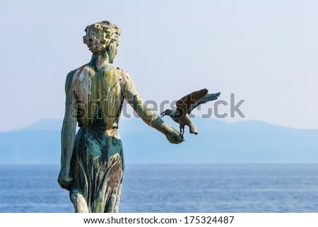 OPATIJA, CROATIA - APRIL 29, 2007: Maiden with the seagull statue with the Adriatic sea in the background. Statue by Zvonko CAR has turned into one of the symbols of Opatija. - stock photo