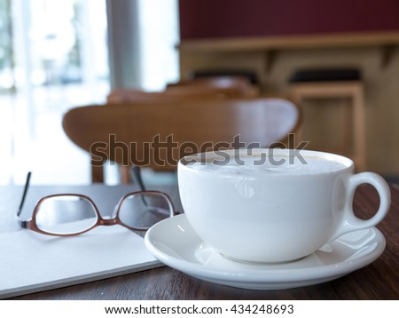 Open a blank white notebook and glasses with hot coffee on table, Selective focus - stock photo