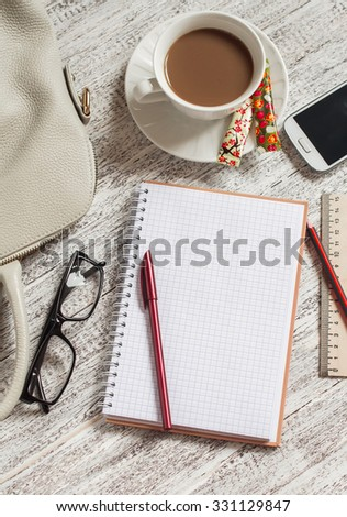 Open a blank white notebook, pen, women's bag, phone, ruler, pencil and cup of coffee on the white desk - stock photo