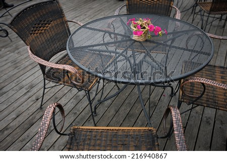 Open-air cafe furniture, wicker chairs and metallic table - stock photo
