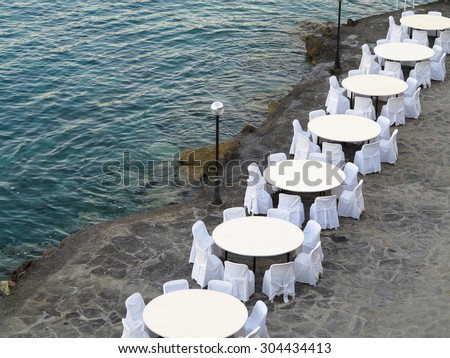 Open air restaurant near sea- white chairs and tables - stock photo