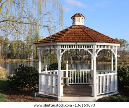 Open air wooden gazebo overlooking a pond an ideal place for picnics, photo shoots and engagement pictures - stock photo