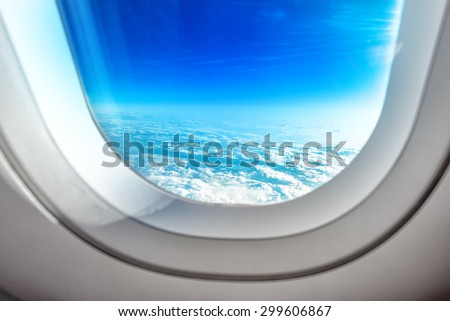 Open Aircraft Airplane Porthole Window and Summer Clouds with Bright Sun Flare - stock photo