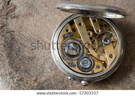 Open antique pocket watch lying on a ceramic grunge background - stock photo