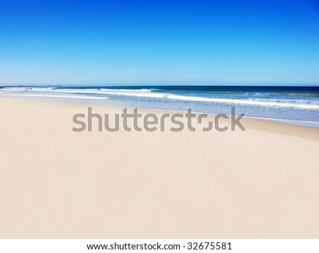 Open beach with blue water and sky - stock photo