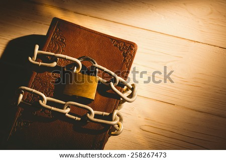 Open bible chained with lock on wooden table - stock photo