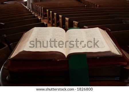 Open bible facing pews - stock photo