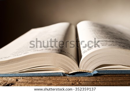 open bible on the table, shallow depth of field - stock photo