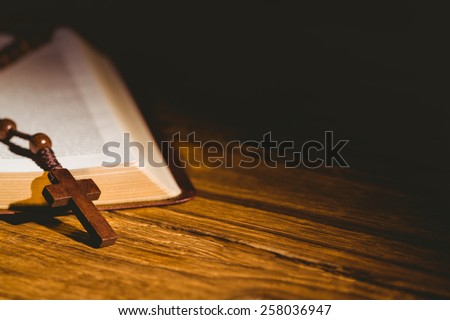 Open bible with rosary beads on wooden table - stock photo