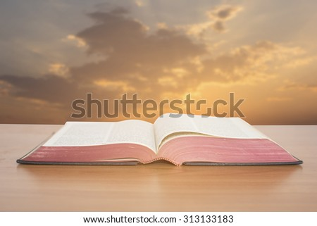 open bible with sunset sky - stock photo
