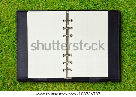 Open Black Cover Binder on Green Grass Background - stock photo