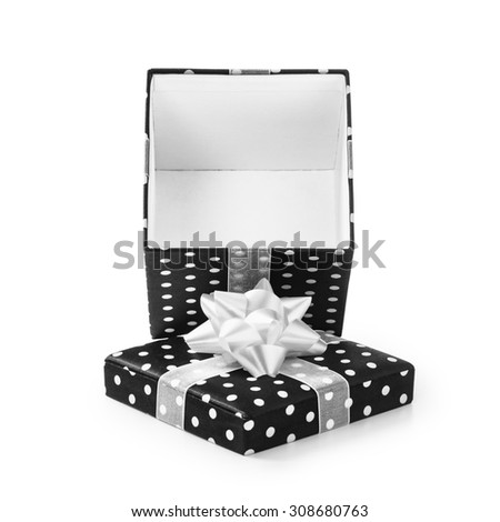 Open black gift box with white dots and ribbon bow. Holiday present. Object isolated on white background. Clipping path - stock photo