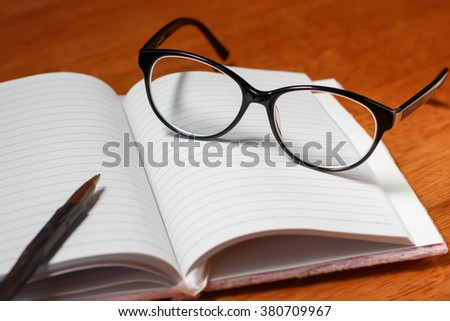 Open blank notebook, pencil and glasses - stock photo