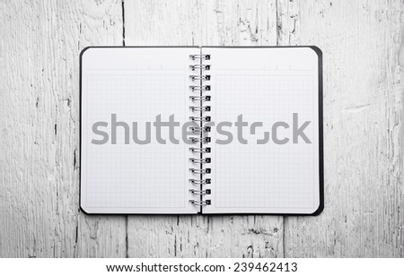 Open blank notepad with empty white pages laying on a wooden table  - stock photo